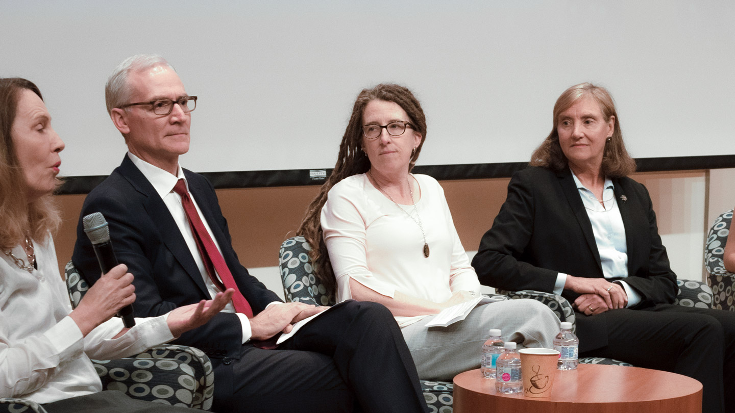 Katie Pollard sitting on a stage with 3 other people during a panel