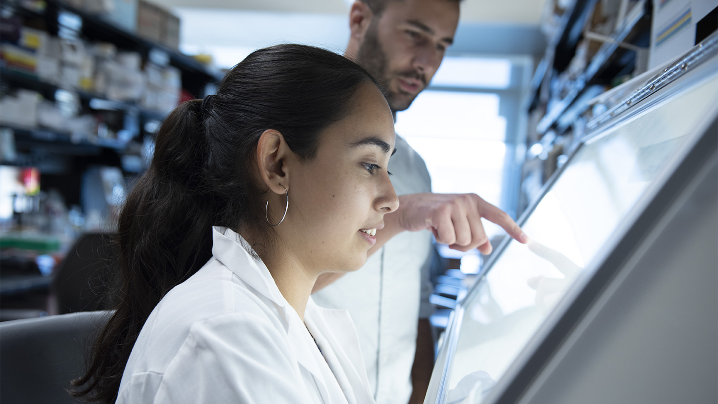 Vanessa Arreola at a lab bench with her mentor Andrea Gramatica pointing to something